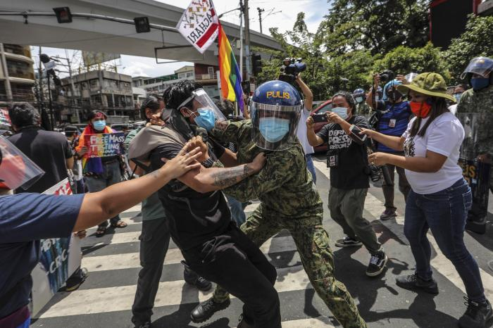 Police wearing face masks arrest protesters during a LGBTQ pride march in Manila, Philippines, Friday June 26, 2020.