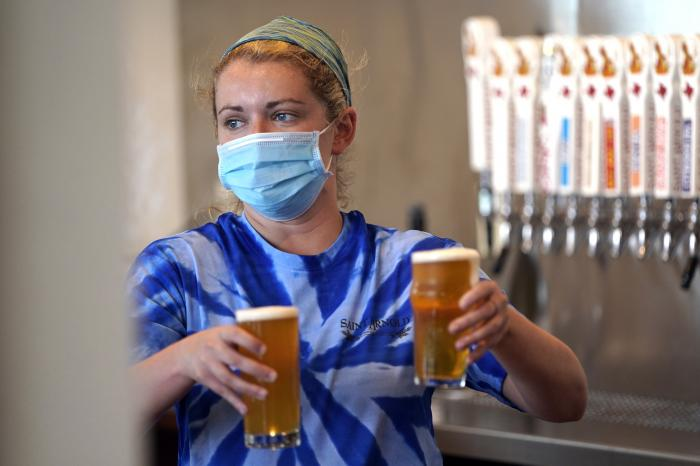 Bartender Katie McGranahan serves beers at the Saint Arnold Brewing Company, Friday, June 26, 2020, in Houston.
