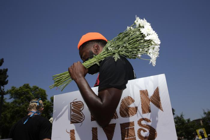 In this July 20, 2020, file photo, holding flowers and a sign, Blair Toles, 30, attends rally in Los Angeles, on Black Strike Day.