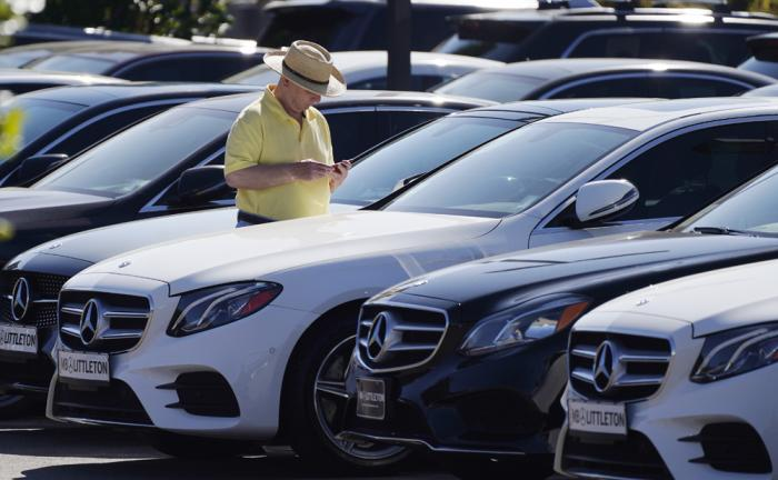 A shopper looks over a long line of 2020 sedans at a Mercedes Benz dealership Sunday, Oct. 4, 2020, in Littleton, Colo.