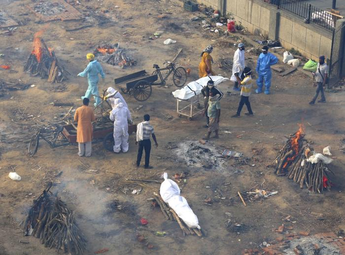 Multiple funeral pyres of those patients who died of COVID-19 disease are seen burning at a ground that has been converted into a crematorium for mass cremation of coronavirus victims, in New Delhi, India.